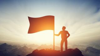 頂上にいる旗を持った男性